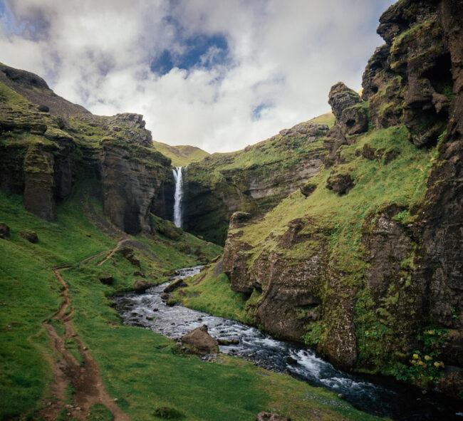 Wasserfall und kleiner Flusslauf im Grünen