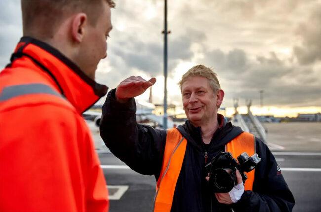 Ein Mann mit Kamera erklärt einem Mann etwas