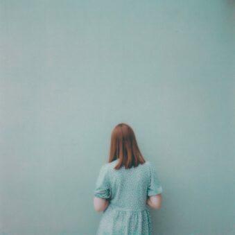 Person in blauem Kleid vor blauer Wand
