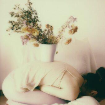 Person mit Blumentopf auf dem Rücken
