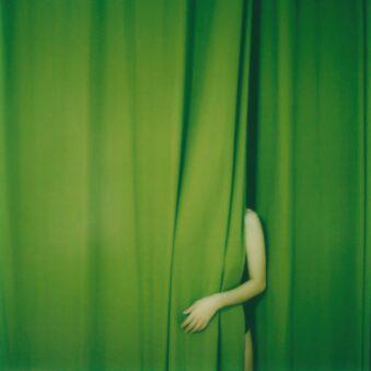 Arm kommt aus grünem Vorhang
