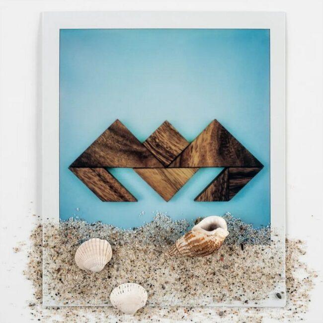 Polaroid einer Krabbenfigur mit Sand und Muscheln