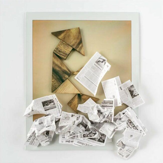 Polaroid einer Figur als Person mit Zeitungen
