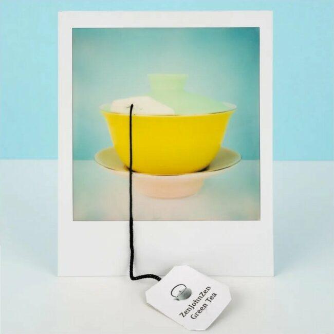 Polaroid einer Teekanne mit aus dem Bild hängengen Teezettel