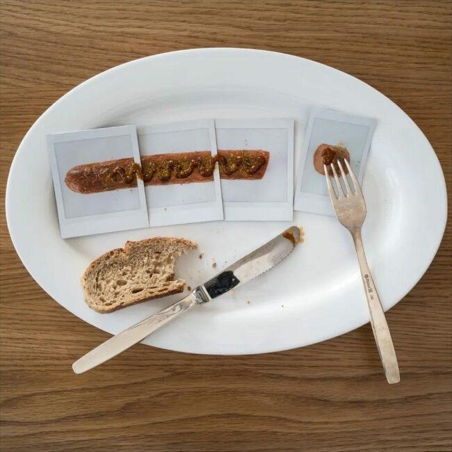 Polaroids einer Wurst liegen mit Besteck und Brot auf einem Teller