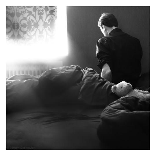 Ein Mann sitzt traurig am Bettrand