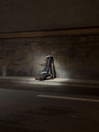 Person im Lichtschein einer Unterführung mit dem Kopf nach unten liegend