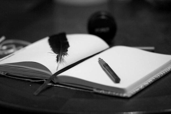 offenes Notizbuch mit Feder und Stift