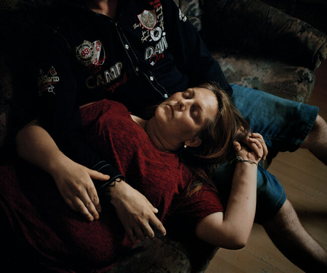 Frau liegt mit dem Kopf auf dem Schoß einer anderen Person