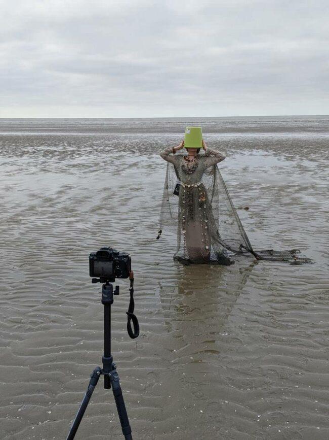 Person am Strand mit Kamera und Eimer auf dem Kopf