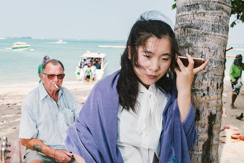 Frau am Handy, ein Mann im Hintergrund