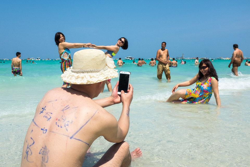 Menschen am Strand machen Fotos