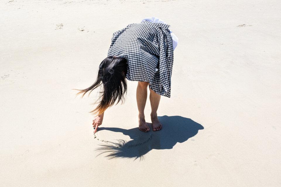 Eine Frau malt etwas in den Sand