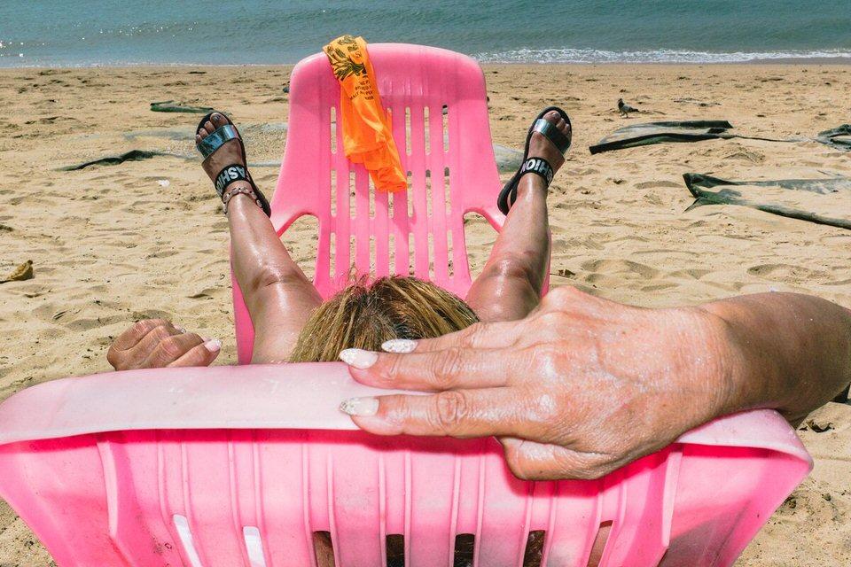 Eine Person auf pinken Plastikstühlen am Strand
