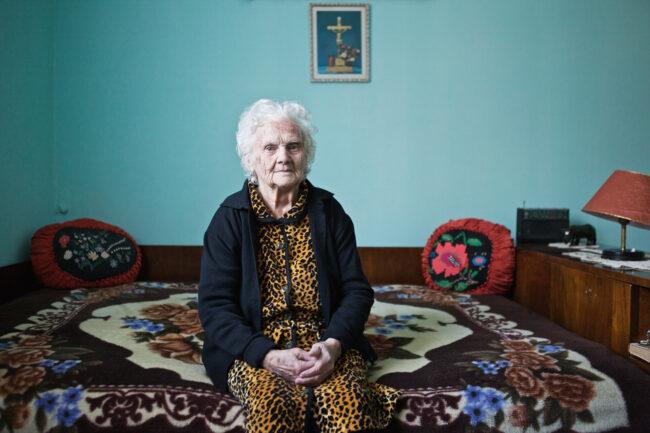 Frau sitzt auf einem Bett mit Kreuz an der Wand